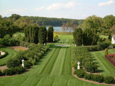 A view from the house to the Miles River, down the central lawn path of Alice Ryan's gardens at Knightly in Easton.
