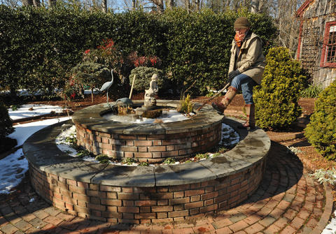 Chris Killian of Annapolis breaks up ice to keep the bubbler flowing in the perennial garden fountain during winter.
