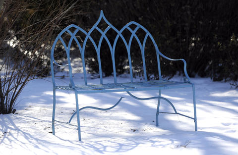 This blue bench is striking against the snow in the winter garden of Alice Ryan of Easton.
