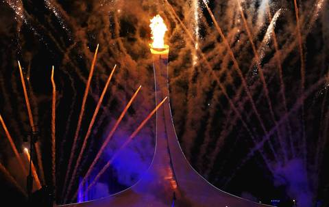 Fireworks explode while the Olympic flame is lit during the Opening Ceremony of the Sochi 2014 Winter Olympics.