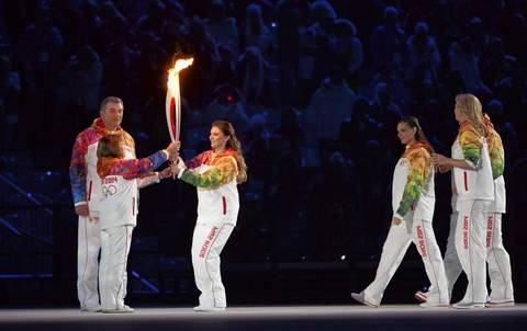 Alina Kabaeva, center, hands off the torch to Irina Rodina and Vladislav Tretyak for the final leg of the torch relay to conclude the opening ceremony.