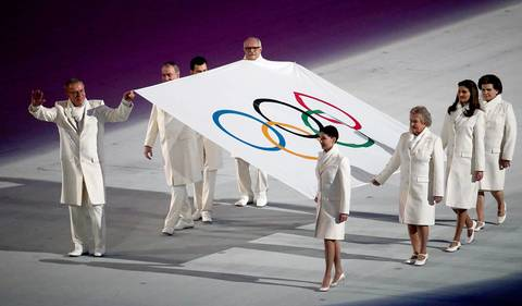 Flag bearers escort the Olympic flag during the opening ceremony for the Winter Olympics.