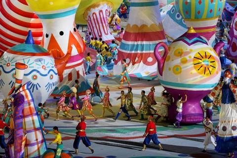 Costumed performers move through symbols of Russian folk arts at Fisht Olympic Stadium.