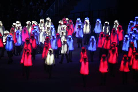 Performers costumed in illuminated red, white and blue outfits prepare to form the Russian national flag during the opening ceremony for the Winter Olympics.