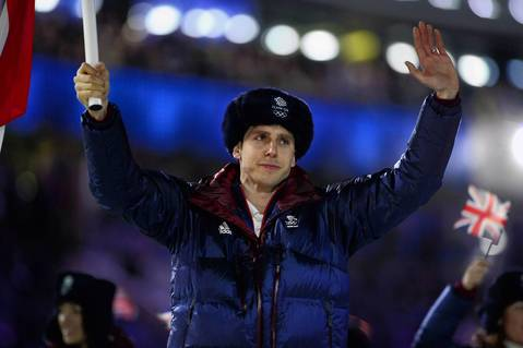 Great Britain's flag bearer, speed skater Jon Eley waves as he leads his delegation during the opening ceremony