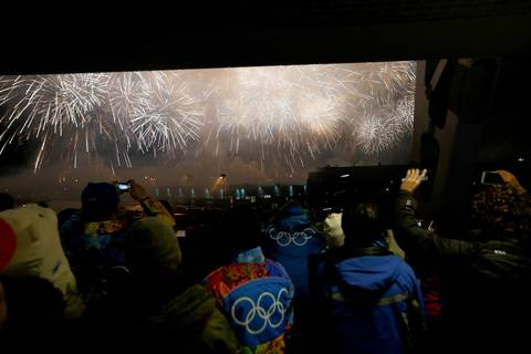 Spectators watch as fireworks go off outside Fisht Olympic Stadium during the opening ceremony.