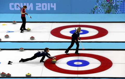 U.S. curler Erika Brown, right, watches teammate Jessica Hultz during curling training at the Ice Cube.