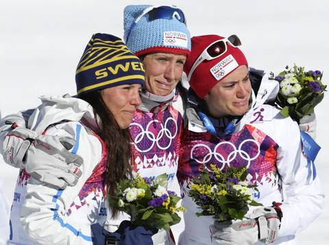 Gold medalist Marit Bjoergen, center, of Norway, celebrates during the flower ceremony with silver medalist Charlotte Kalla, left, of Sweden, and bronze medalist Heidi Weng, of Norway, after the ladies' skiathlon 7.5 km Classic + 7.5 km free in the Laura Cross-country Ski & Biathlon Center