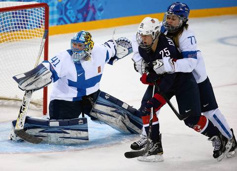 Finland's goalkeeper Noora Raty (41) defends the net as teammate Susanna Tapani (77) restrains U.S. forward Alex Carpenter (25) during the first period in a women's hockey game.