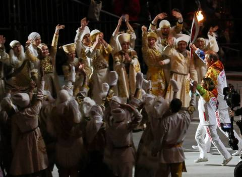 Vladislav Tretiak and Irina Rodnina carry the Olypmic torch out of Fisht Olympic Stadium and head to the Olympic cauldron during the opening ceremony for the Winter Olympics.