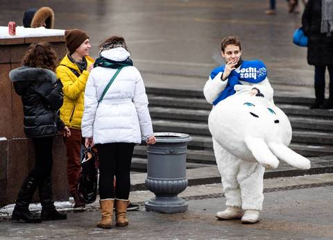 A street artist dressed as the white rabbit, one of the mascots of the 2014 Winter Sochi Olympics, smokes in the center of Moscow.