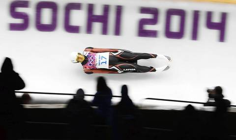 Kristaps Maurins of Latvia speeds past spectators in his first run in the men's singles luge at the Sanki Sliding Center.