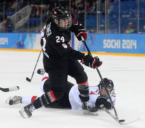 Canada forward Natalie Spooner (24) shoots over Switzerland defenseman Angela Frautschi (11) during the third period in a women's hockey game at the Winter Olympics.