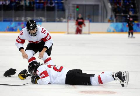 Switzerland defenseman Laura Benz falls to the ice with an injury against Canada during the third period in a women's hockey game at the Winter Olympics. Canada defeated Switzerland 5-0.