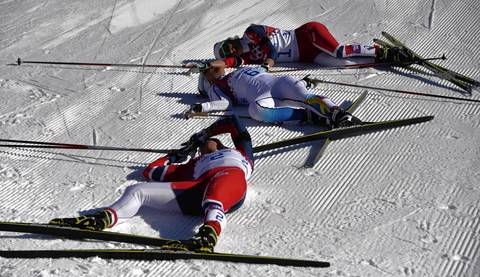 Norway's Marit Bjoergen, bottom, Sweden's Charlotte Kalla and Norway's Therese Johaug lie on the track after the women's cross-country skiing 7,5km + 7,5km skiathlon at the Laura Cross-Country Ski and Biathlon Center.