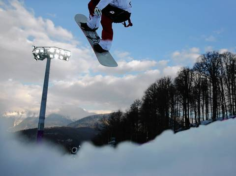 "Brad Martin, of Canada, competes in a qualifying round for the men's halfpipe at the Rosa Khutor Extreme Park. ""I walked to several points up and down the right side of the hill during qualifying and semifinals to get a feel for it, but there is no one perfect spot for every competitor. The nice part of this is that the photographers are spread out so you all get different pictures. I tried some wide angle images with my camera in the snow and under the fence, shooting one boarder right in front and another that I caught just his feet. I also tried a whole range of lenses from 24 to 400 to shoot competitors on different parts of the course. The backdrops had a nice view of mountains and trees early when you could find a spot where there weren't TV cables overhead."""