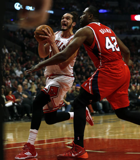 Joakim Noah drives past the Hawks' Elton Brand in the second quarter.