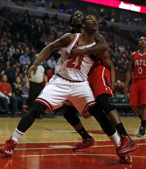 Jimmy Butler and the Hawks' DeMarre Carroll vie for rebounding position in the 1st quarter.