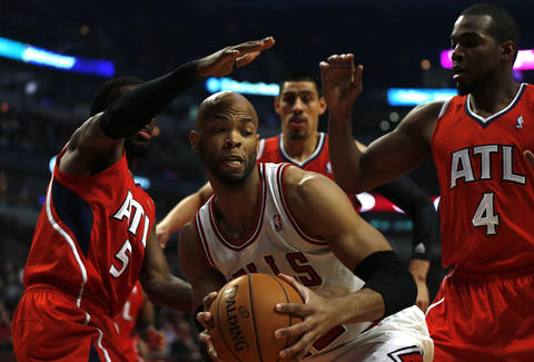 Taj Gibson tries to escape from a trap by the Hawks' DeMarre Carroll and Paul Millsap (4) in the first quarter.