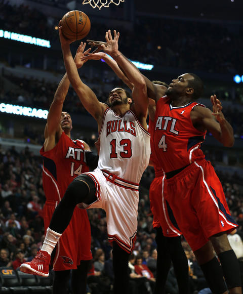 Joakim Noah splits the defense of the Hawks' Paul Millsap (4) and Gustavo Ayon in the 1st quarter.