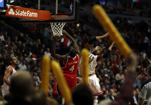 Taj Gibson grabs a rebound against the Hawks' Paul Millsap in the 3rd quarter.
