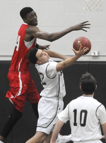 Fairfield Prep's Paschal Chukwu, 44, forces Xavier High School's Kaleb Lutton, 12, to force a shot during the third period.
