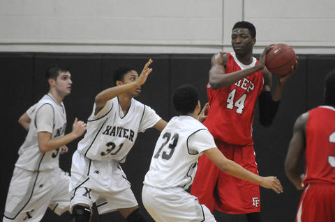 Fairfield Prep's Paschal Chukwu, 44, looks to pass as he is defended by three Xavier players, from left,  Xavier High School's Brandon MacPherson, 33, Xavier High School's Alex White, 31, and Xavier High School's Kaleb Downing, 23, during the second period.