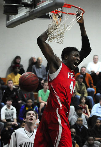 Fairfield Prep's Paschal Chukwu, 44, reacts after scoring on a dunk during the fourth period as Xavier High School's Joe McCormack, 10, looks on.