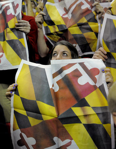 Maryland fan Zoe Kersner's eyes gaze above a newspaper as Duke's players are introduced.