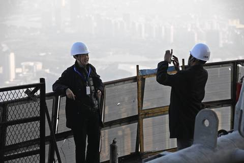 Gensler senior project architect Michael Peng, left, poses for a photograph as he leans on a wire mesh fence on the 111th floor of the under-construction Shanghai Tower in the Pudong district of Shanghai.