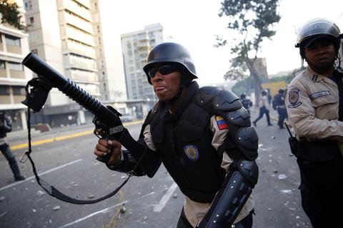 Riot police shoot tear gas as they fight against students during a protest against President Nicolas Maduro's government in Caracas February 15, 2014. Protesters gathered to demand the president's resignation, denouncing him over grievances ranging from political repression to daily issues such as inflation, shortages of basic products, and rampant crime.