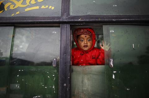 A child reacts as she looks out from the window of a passenger bus that stalled on Bhimdatta Pant Highway during heavy snowfall in the far western region of Nepal, around 800 km (497 miles) from Kathmandu February 15, 2014. Sudden heavy snowfall obstructed traffic on the highway on Saturday, causing travel delays and leaving thousands of passengers stranded, according to the local Nepal Police rescue team.