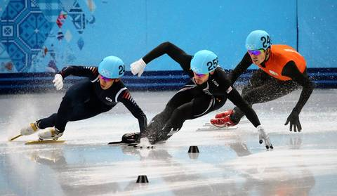 "South Korea's Ho-Suk Lee (left) touches the skate of the USA's Eduardo Alvarez (center), causing both to fall in a semifinal of the men's 5000m short track. ""I learned a lot about two new sports today. There was a short track speed skating session with about 17 different heats and qualifiers. The sport is known for its crashes on the tight turns, so I chose a spot facing the far curve. This worked well in the men's semifinal relay when the Korean and USA teams collided and wrecked into a wall. In the take afterwards I was able to see the Korean skater's hand pull the American's skate on the way down, leading to a disqualification for the Korean team and a judges decision to advance the U.S. to the finals anyway."""