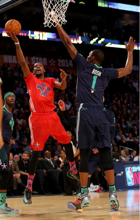 The Western Conference's Kevin Durant of the Thunder takes a shot as the Eastern Conference's Chris Bosh of the Heat defends.