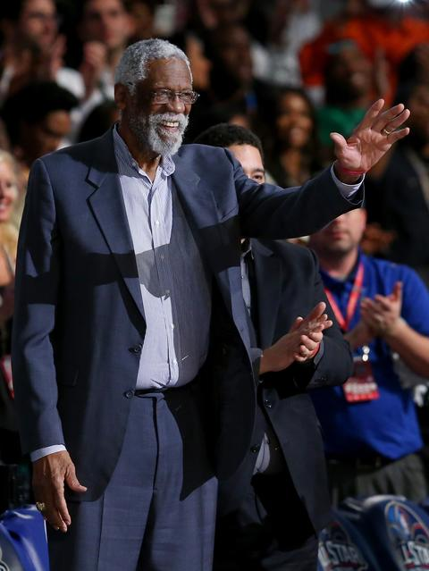 NBA legend Bill Russell salutes the fans during the first half of the game.