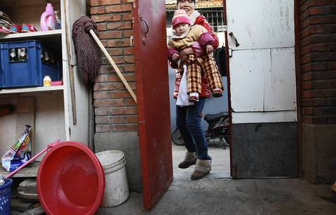 Cai Qun, 26, carries her 14-month-old son into a family courtyard in the Paoju Hutong in Beijing. American homes are surrounded by lawns and other open space. However, in China, the courtyard homes enclose open space.