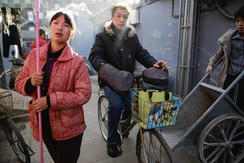 Fan Xinghua, 35, left, talks about life in the Paoju Hutong in Beijing. Homes in hutongs range from rehabbed, fully modernized places for professionals to primitive, overcrowded homes for migrant families. Few have central heating or plumbing. Many residents must walk to a public toilet as well as a public shower.