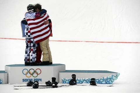 Nikolay Olyunin, left, of Russia, Pierre Vaultier, middle back, of France and Alex Deibold, right, of the U.S. embrace during the flower ceremony after the big final run of the men's snowboard cross finals.