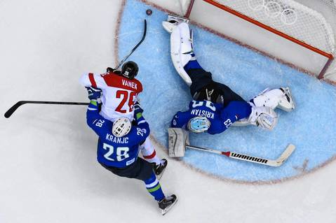 Austria's Thomas Vanek, center, tries to score against Slovenia's goalkeeper Robert Kristan, right, and Slovenia's Ales Kranjc, left, during the men's ice hockey playoffs.