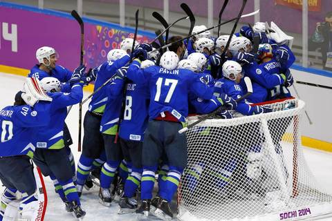 Slovenia players celebrate after defeating Austria in a men's ice hockey playoffs qualifications game at Bolshoy Ice Dome.