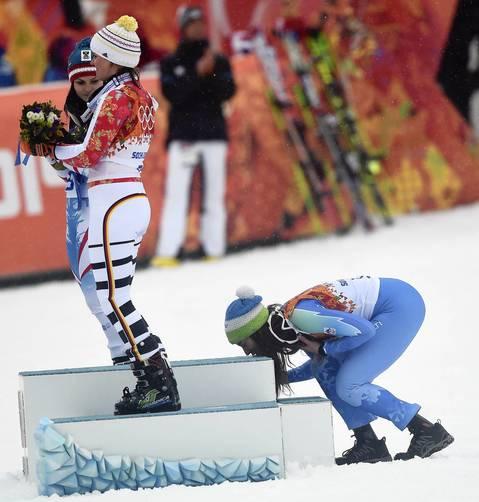 Tina Maze, of Slovenia, right, kisses the podium as she celebrates her gold medal during the flower ceremony for the Women's Giant Slalom at the Rosa Khutor Alpine Center. Also on the podium are Anna Fenninger, left, and Viktoria Rebensburg, center.