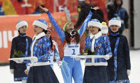 Tina Maze, of Slovenia, celebrates her gold medal during the flower ceremony for the ladies giant slalom.