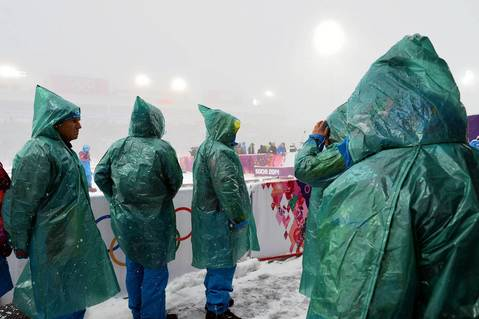 Volunteers stand in the snow as the start of the men's biathlon 15k mass start is delayed at the Laura Cross-Country Ski and Biathlon Center.