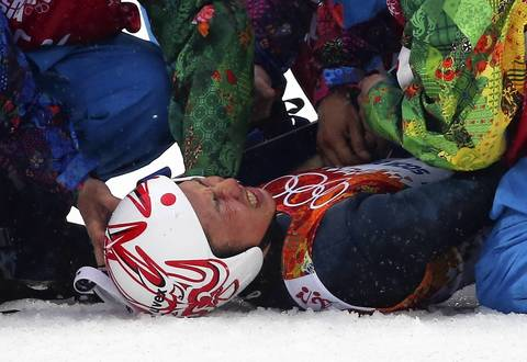 Taihei Kato, of Japan, is treated by medical staff after crashing during the Nordic combined men's individual LH at RusSki Gorki Jumping Center.