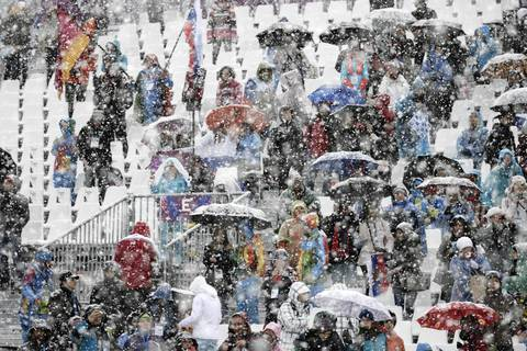 Fans weather the snow at the men's ski halfpipe qualification round at Rosa Khutor Extreme Park.