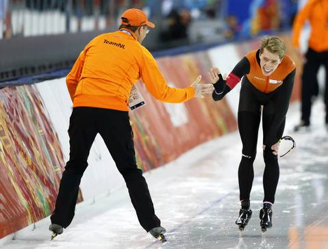 Jorrit Bergsma, of the Netherlands, celebrates with his coach after competing in the men's 10,000 meter speed skating event.