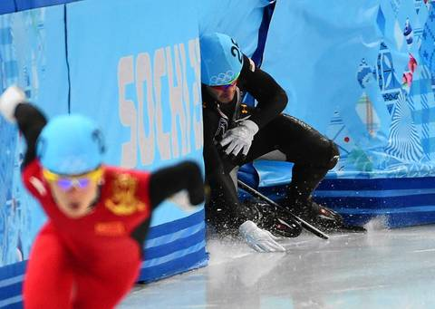 USA's Eduardo Alvarez (256) loses his balance and crashes into the wall during a turn during the men's 500 meter speed skating race at the Iceberg Skating Palace