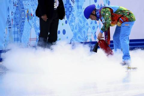 A volunteer resurfaces the rink during the short track men's 500m heat at Iceberg Skating Palace.