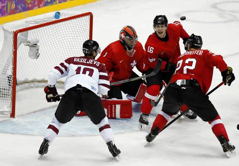 Switzerland's defenseman Rafael Diaz (16) looks at the puck in front of goalie Jonas Hiller (1) in a men's ice hockey playoffs qualifications game against Latvia.
