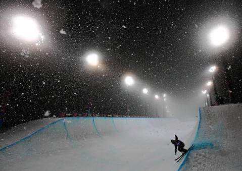 Skiers warm up in heavy snow for the finals of the men's ski halfpipe at Rosa Khutor Extreme Park.